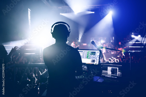 Photo Sound engineer music producer adjusting and balancing audio on rock concert, sil