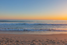 Sunset Over Ocean Waves And Beach
