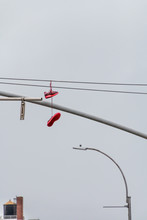 A Pair Of Red Shoes Are Hangin...