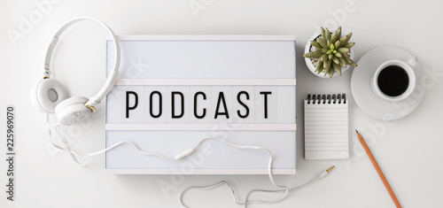 Fototapeta Podcast word on lightbox with headphones, notepad and coffee cup, flat lay