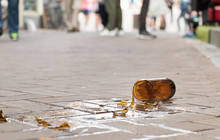 A Brown Glass Bottle Of Beer Broken On The Floor Of The Sidewalk Street.