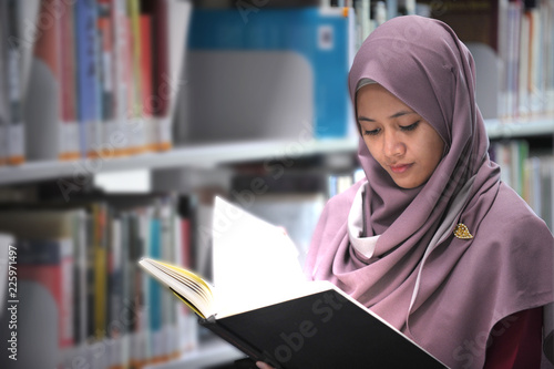 Fotomural  Young hijab student reading a book in a public library.