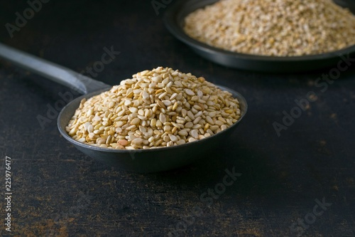 A close up of a metal spoon full of sesame seeds on a rustic metal surface