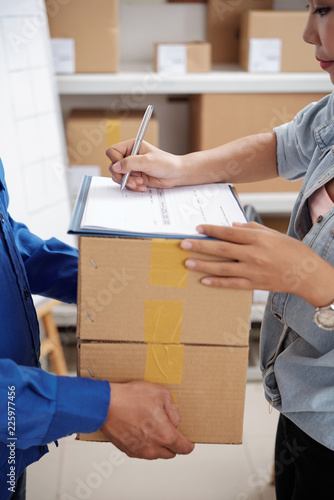 Cuadros en Lienzo Delivery service manager signing document and taking parcels from courier