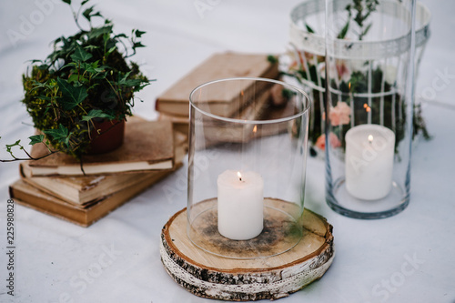 Obraz Table for wedding ceremony is decorated with flowers, cage, candles, books and greens, greenery. Compositions of wedding wooden decor in the backyard banquet area. Close up. Artwork in style vintage. - fototapety do salonu