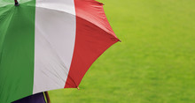 Italy Flag Umbrella. Close Up Of Printed Umbrella Over Green Grass Lawn / Field. Rainy Weather Forecast Concept.