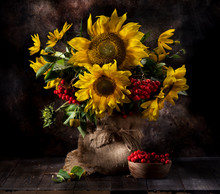 Still Life With Sunflowers And Autumn Flowers In A Vase On A Wooden Background