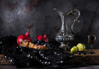 Still life with a jug of wine, grapes and pomegranates on a dark concrete background