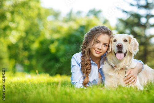 Young woman with golden retriever dog in the summer park Canvas
