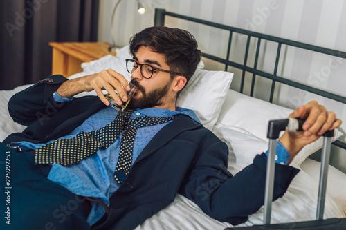 Plakat Zmęczony biznesmen odpoczywa w pokoju hotelowym