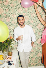 Portrait Of Smiling Young Man Holding Drink While Standing By Woman With Balloons Against Wallpaper At Home During Dinne