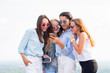Four young women in sunglasses use smartphone standing on the roof of the building. Friendship and modern technology concepts