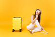 Traveler tourist woman in summer casual clothes, hat sit with suitcase isolated on yellow orange background. Female passenger traveling abroad to travel on weekends getaway. Air flight journey concept