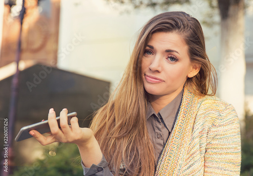 Fotografie, Obraz  annoyed sad woman with mobile phone standing outside in the street