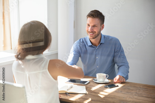 Two Businesspeople Shaking Hands Over Wooden Desk Canvas-taulu