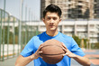 young asian man holding a basketball