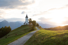 Church On The Hill At Sunrise. Beautiful Scenery At Jamnik, Slovenia. Panoramic View Of The Alps Behind The Church.