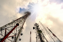 Telecommunication Center,low Angle View..Group Of Antenna Tower On Hill Top Include Of Television Radio And Microwave With Sunray In Cloud Blue Sky ,lens Flare Effect..