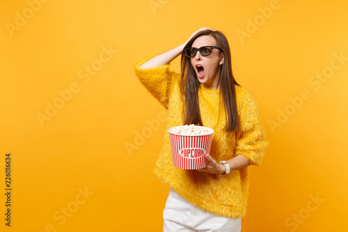 Photo  Shocked indignant young girl in 3d imax glasses putting hand on head, screaming watching movie film, hold bucket of popcorn isolated on yellow background