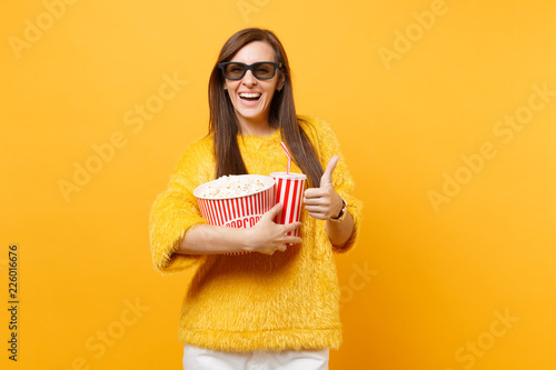 Photo Joyful young woman in 3d imax glasses watching movie film, holding bucket of popcorn, cup of cola or soda, showing thumb up isolated on yellow background