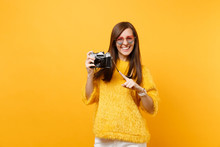 Portrait Of Smiling Young Woman In Heart Glasses Pointing Index Finger On Retro Vintage Photo Camera Isolated On Bright Yellow Background. People Sincere Emotions, Lifestyle Concept. Advertising Area.