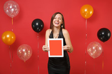 Laughing Young Girl In Black Dress Celebrating, Holding Tablet Pc Computer With Blank Black Empty Screen On Bright Red Background Air Balloons. Happy New Year, Birthday Mockup Holiday Party Concept.