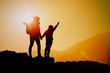 Silhouettes of happy mother and son hiking at sunset