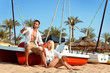 handsome man and blond woman enjoying their vacation on a sunny sand beach sitting on a boat, they are happy on summer day. a couple in love having fun on an island, beautiful family likes o travel