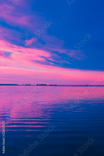 Beautiful pink sunset over lake. Nature landscape background