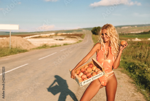 sensual girl with blond hair in elegant swimming suit posing with box of fresh peaches