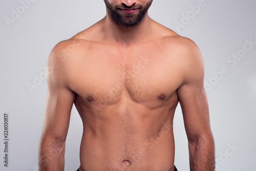 Obraz Perfection. Part of handsome shirtless young man standing against white background - fototapety do salonu