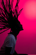 canvas print picture - silhouette of african man with flying dreadlocks in profile on red background