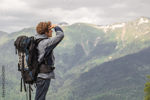 Fototapeta awesome touris is standing on the peack of the mountain and enjoying the breathtaking scenery. copyspace. extreme sport concept obraz