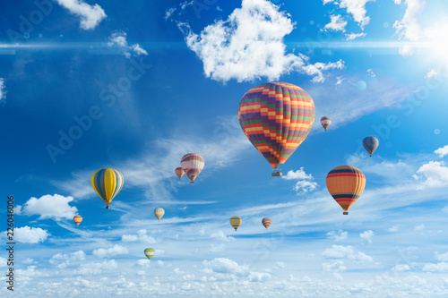 Colorful hot air balloons fly in blue sky with white clouds and bright sunshinr