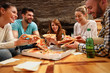 canvas print picture - Group of young people eating's big pizza together