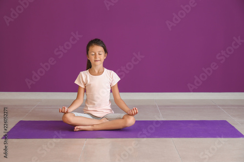 Little girl practicing yoga indoors