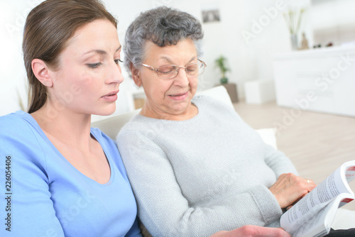 Photo young female caregiver reading a story to the old woman