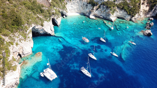 mata magnetyczna Aerial drone bird's eye view photo of sail boats docked in tropical caribbean paradise bay with white rock caves and turquoise clear sea