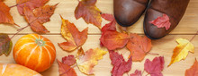 Banner Autumn Mood. Shoes Boots And Autumn Leaves With Pumpkin On Wooden Background. Concept Lifestyle. Top View