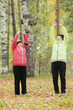 Mature woman in colourful jackets doing gymnastics in an autumn park after a scandinavian walk. Arms up