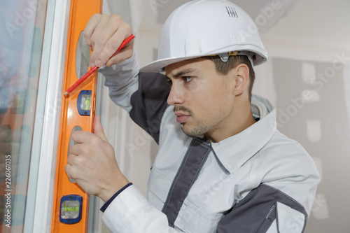 Fotografie, Obraz  young worker marking on wall with level