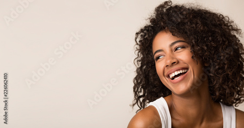 Fototapety, obrazy: Laughing african-american woman looking away on light background