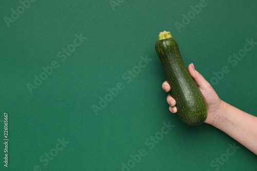 Fresh zucchini in female hand on green background