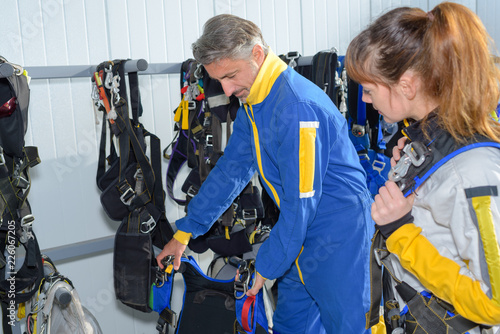 male instructor with female student preparing before skydiving