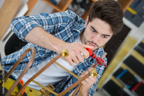 Worker clamping copper pipe Fototapeta