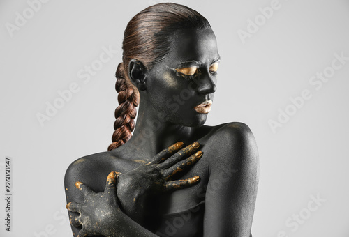 Fototapeta Beautiful woman with black and golden paint on her body against light background obraz na płótnie