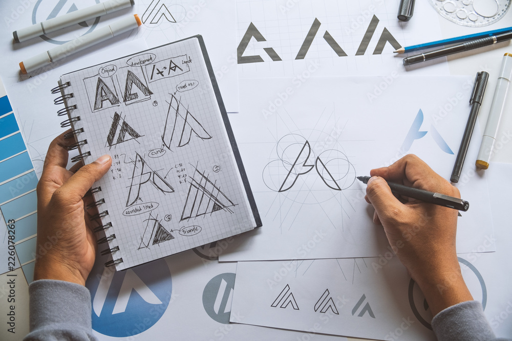 Fototapeta Graphic designer development process drawing sketch design creative Ideas draft Logo product trademark label brand artwork. Graphic designer studio Concept.