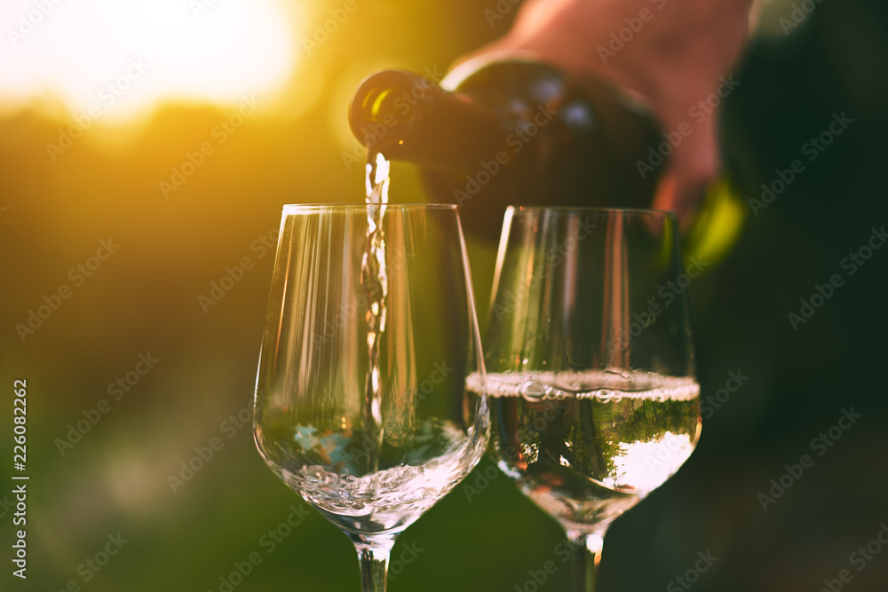 Pouring white wine into glasses at sunset