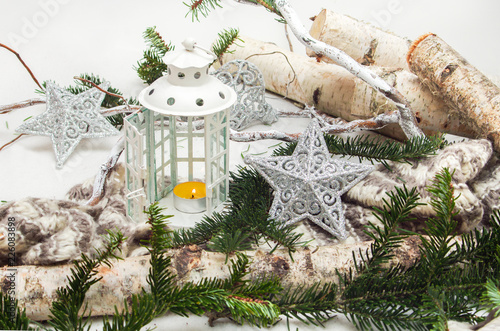 Photo  winter composition white decorative lantern and gray stars with sprigs of Christ
