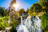 Landscape with waterfall in the forest and bright sun shining through the trees